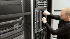 IT technician removes harddrive from blade server in datacenter stock video