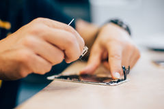 Technician repair faulty mobile phone in electronic smartphone t. Echnology service. Cellphone technology device maintenance engineer Royalty Free Stock Images