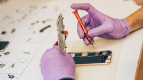 Technician repair faulty mobile phone in electronic smartphone t. Echnology service. Cellphone technology device maintenance engineer stock photo