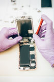 Technician repair faulty mobile phone in electronic smartphone t. Echnology service. Cellphone technology device maintenance engineer Royalty Free Stock Image