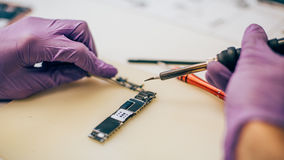Technician repair microchip and motherboard of mobile phone in e Stock Photos
