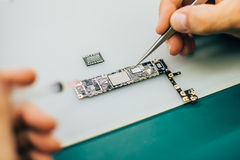 Technician repair microchip and motherboard of mobile phone in e Royalty Free Stock Photos