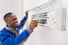 Technician Repairing Air Conditioner. Happy Young African Male Technician Repairing Air Conditioner Stock Photography