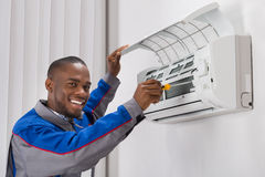 Technician Repairing Air Conditioner. Happy Young African Male Technician Repairing Air Conditioner Royalty Free Stock Images