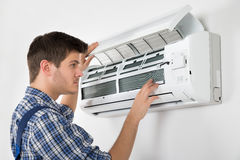 Technician Repairing Air Conditioner. Photo Of Young Male Technician Repairing Air Conditioner Royalty Free Stock Photography