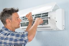 Technician repairing air conditioner. Portrait Of Mid-adult Male Technician Repairing Air Conditioner Stock Photography