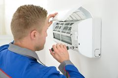 Technician repairing air conditioner. Portrait Of Young Male Technician Repairing Air Conditioner Royalty Free Stock Photography