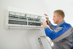 Technician repairing air conditioner. Portrait Of Young Male Technician Repairing Air Conditioner Royalty Free Stock Images