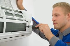 Technician repairing air conditioner. Portrait Of Young Male Technician Repairing Air Conditioner Royalty Free Stock Photos