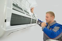 Technician repairing air conditioner. Portrait Of Young Male Technician Repairing Air Conditioner Royalty Free Stock Image
