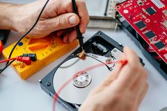 Technician repairing broken hard disk drive. Data recovery concept Stock Image