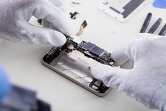 Technician Repairing Broken Mobile Phone. Close-up Of Person`s Hand Wearing Glove Repairing Cellphone stock photography