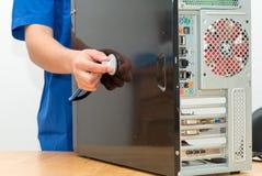 Technician repairing broken pc desktop computer with stethoscope. A technician repairing broken pc desktop computer with stethoscope Stock Photography