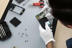 Technician repairing broken smartphone at table. Closeup royalty free stock photos