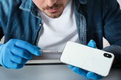 Technician repairing broken smartphone at table. Closeup royalty free stock images