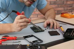 Technician repairing broken smartphone at table. Closeup stock image