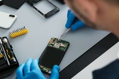 Technician repairing broken smartphone at table. Closeup royalty free stock photo