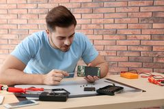 Technician repairing broken smartphone at table. In workshop stock photos