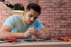 Technician repairing broken smartphone at table. In workshop royalty free stock images
