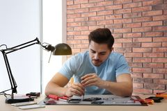 Technician repairing broken smartphone at table. In workshop royalty free stock photos
