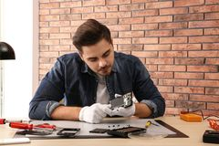 Technician repairing broken smartphone in workshop. Technician repairing broken smartphone at table in workshop stock image