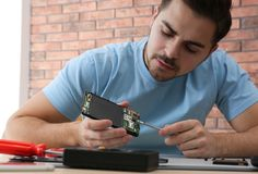 Technician repairing broken smartphone in workshop. Technician repairing broken smartphone at table in workshop royalty free stock photography