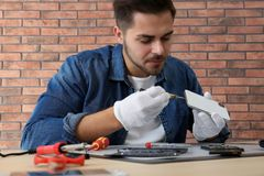 Technician repairing broken smartphone at table. In workshop royalty free stock image
