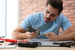Technician repairing broken smartphone at table. In workshop stock photo