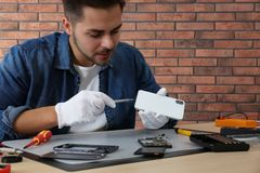 Technician repairing broken smartphone at table. In workshop royalty free stock photography