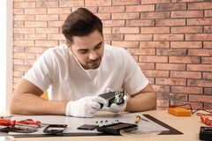 Technician repairing broken smartphone at table in workshop. Space for text royalty free stock photos