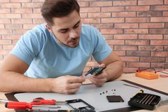 Technician repairing broken smartphone in workshop. Technician repairing broken smartphone at table in workshop stock images