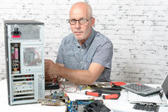 A technician repairing a computer. With different tools Royalty Free Stock Photography