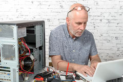 A technician repairing a computer. With different tools Royalty Free Stock Photo