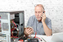 A technician repairing a computer and phone. To the customer Royalty Free Stock Images
