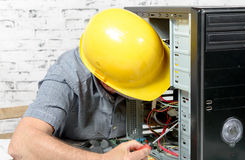 A technician repairing a computer with yellow helmet Stock Image