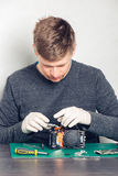 Technician repairing digital camera. Technician in latex gloves repairing digital camera in a service laboratory Stock Photography