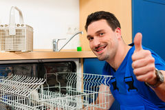 Technician repairing the dishwasher Stock Photography
