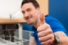 Technician repairing the dishwasher Royalty Free Stock Photo
