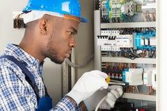 Technician Repairing Fusebox With Screwdriver Stock Photo