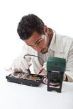 Technician repairing a hard disk. A technician repairing an hard disk with a tester Royalty Free Stock Image