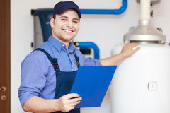 Technician repairing an hot-water heater Stock Photos