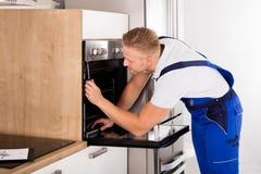 Technician Repairing Oven Stock Photography
