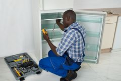 Technician Repairing Refrigerator Appliance Stock Photo