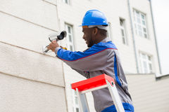 Technician Repairing Surveillance Camera. Young Happy Male Technician On Ladder Repairing Surveillance Camera Royalty Free Stock Photo