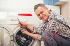 Technician repairing a washing machine Stock Photos