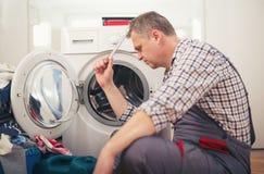 Technician repairing a washing machine Royalty Free Stock Image