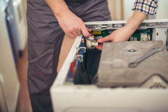 Technician repairing a washing machine Royalty Free Stock Images