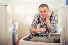 Technician repairing a washing machine Stock Images