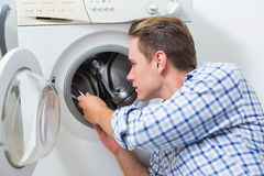 Technician repairing a washing machine Stock Images