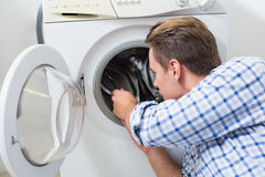 Technician repairing a washing machine Royalty Free Stock Image